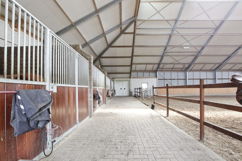 een vrijstaande woonboerderij met inpandig stalgedeelte en een fraai aangelegde tuin, een vrijstaande rijhal met paardenstallen, een buitenbak, een veldschuur en diverse paddocks met een grasbodem